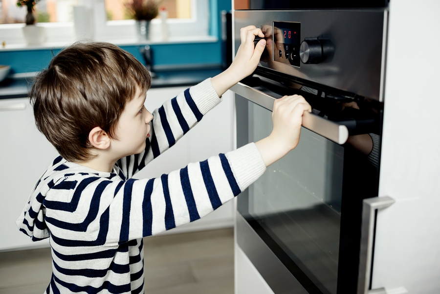 Boy Dangerously Playing With The Knobs On The Oven