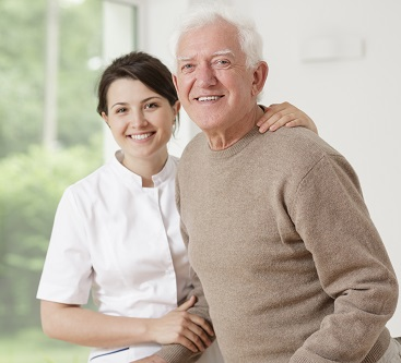 elderly man being helped by a nurse